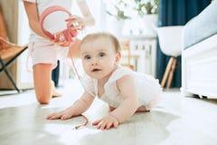 Bebé joven lindo que se sienta en el piso en casa que juega con los auriculares Fotos de archivo libres de regalías