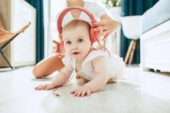 Bebé joven lindo que se sienta en el piso en casa que juega con los auriculares Imagen de archivo