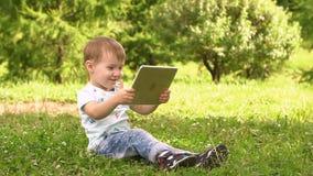 Bebé joven que usa la tableta afuera en el parque almacen de metraje de vídeo