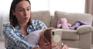 Bebé juguetón con la madre que toma el selfie usando el teléfono en casa almacen de metraje de vídeo