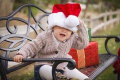Bebé juguetón que lleva a Santa Hat Sitting con los regalos de la Navidad afuera Fotos de archivo