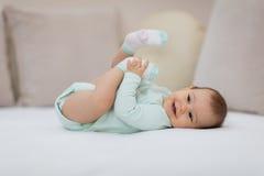 Bebé juguetón que se acuesta en cama Imagen de archivo libre de regalías