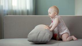 Bebé juguetón que se divierte en el sofá en casa, mundo de descubrimiento infantil activo almacen de metraje de vídeo
