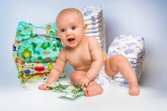 Bebé lindo con el dinero aislado en fondo borroso de los pañales Fotografía de archivo libre de regalías