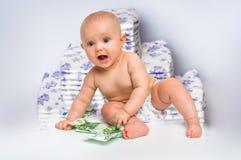 Bebé lindo con el dinero aislado en fondo borroso de los pañales Fotografía de archivo