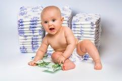 Bebé lindo con el dinero en fondo borroso de los pañales Foto de archivo