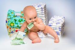 Bebé lindo con el dinero en fondo borroso de los pañales Fotografía de archivo libre de regalías