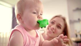 Bebé lindo con el juguete Bebé infantil que mira alrededor Familia cariñosa feliz metrajes