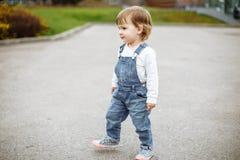 Bebé lindo con el pelo rubio que corre al aire libre Niña 1-2 años imagen de archivo libre de regalías