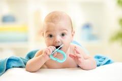 Bebé lindo con el teether debajo de la toalla interior Imagen de archivo