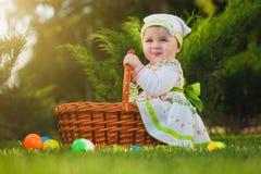 Bebé lindo con la cesta en el parque verde fotografía de archivo