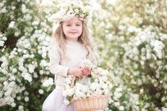 Bebé lindo con las flores en jardín Imagenes de archivo