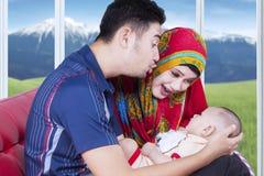 Bebé lindo con los padres que juegan en el sofá foto de archivo libre de regalías