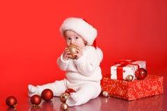 Bebé lindo con los regalos de Navidad y las decoraciones Fotografía de archivo libre de regalías