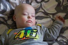 Bebé lindo con Síndrome de Down que duerme en la cama Foto de archivo libre de regalías
