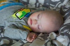 Bebé lindo con Síndrome de Down que duerme en la cama Fotos de archivo libres de regalías