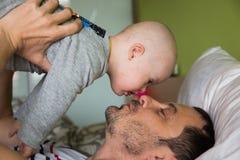 Bebé lindo con Síndrome de Down que juega con el papá Foto de archivo