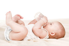 Bebé lindo con una botella de leche en una manta beige Fotografía de archivo