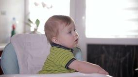 Bebé lindo curioso que mira alrededor, sentándose en silla del bebé Mime a alimentar su de un año adorable con una cuchara almacen de video