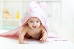 Bebé lindo debajo de la toalla después de bañar en casa Foto de archivo libre de regalías