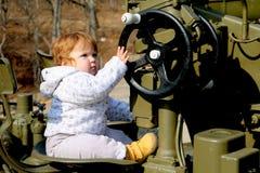 Bebé lindo del jengibre que se sienta en el volante del ejército militar imágenes de archivo libres de regalías