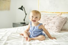 Bebé lindo en cama en casa imagenes de archivo