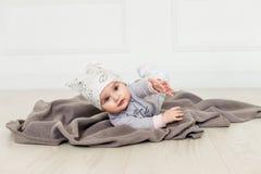 Bebé lindo en el fondo blanco Ciérrese encima del tiro principal de un bebé caucásico, seis meses del bebé en ropa de un gris y Fotografía de archivo libre de regalías