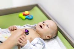 Bebé lindo en el gabinete del ` s del doctor Pediatra que hace el examen de niño con el estetoscopio Niño sano sonriente Niños Imagen de archivo