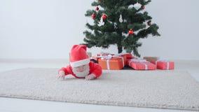 Bebé lindo en el traje de Santa Claus, mirando un regalo almacen de video