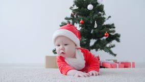 Bebé lindo en el traje de Santa Claus, mirando un regalo almacen de metraje de vídeo