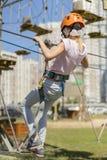 Bebé lindo en engranaje que sube en un fondo del parque de la cuerda La pequeña muchacha hermosa sube en el arnés de la cuerda en Fotos de archivo libres de regalías