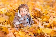 Bebé lindo en hojas de otoño Foto de archivo libre de regalías