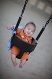 Bebé lindo en un oscilación del patio Foto de archivo