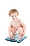 Bebé lindo en una escala del peso, aislada en blanco Imágenes de archivo libres de regalías