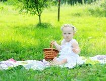 Bebé lindo en una guirnalda en una comida campestre en un día de verano Imagen de archivo