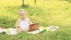 Bebé lindo en una guirnalda en una comida campestre en un día de verano Foto de archivo