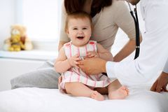Bebé lindo feliz con la madre en el examen de la salud en la oficina del ` s del doctor Concepto de la medicina y de la atención  Imagen de archivo