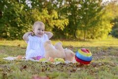 Bebé lindo feliz en un vestido blanco con los juguetes que se sientan en un claro soleado imágenes de archivo libres de regalías