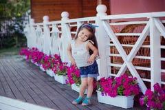 Bebé lindo hermoso elegante con el pelo moreno que presenta en jardín de madera por completo de las flores que llevan las camisas Imagen de archivo