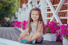 Bebé lindo hermoso elegante con el pelo moreno que presenta en jardín de madera por completo de las flores que llevan las camisas Imágenes de archivo libres de regalías