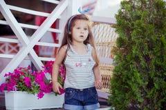 Bebé lindo hermoso elegante con el pelo moreno que presenta en jardín de madera por completo de las flores que llevan las camisas Fotografía de archivo