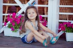 Bebé lindo hermoso elegante con el pelo moreno que presenta en jardín de madera por completo de las flores que llevan las camisas Fotos de archivo libres de regalías