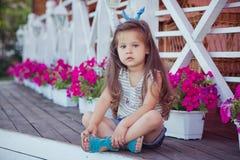 Bebé lindo hermoso elegante con el pelo moreno que presenta en jardín de madera por completo de las flores que llevan las camisas Foto de archivo