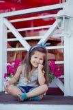 Bebé lindo hermoso elegante con el pelo moreno que presenta en jardín de madera por completo de las flores que llevan las camisas Fotos de archivo