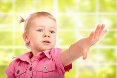 Bebé lindo que alcanza para algo imagen de archivo
