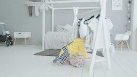 Bebé lindo que aprende colocarse que sostiene encendido la ropa almacen de metraje de vídeo