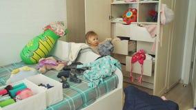 Bebé lindo que arregla la ropa en sitio sucio metrajes