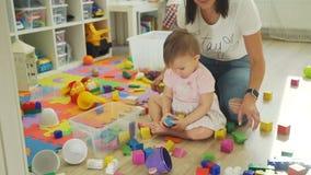 Bebé lindo que ayuda a su madre a coger los juguetes metrajes