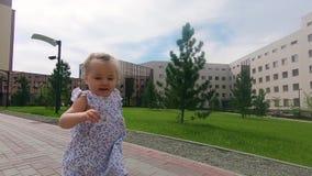 Bebé lindo que camina en hierba en el parque de la ciudad, cámara lenta almacen de video