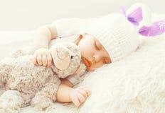 Bebé lindo que duerme con el juguete del oso de peluche en la cama suave blanca Fotografía de archivo libre de regalías
